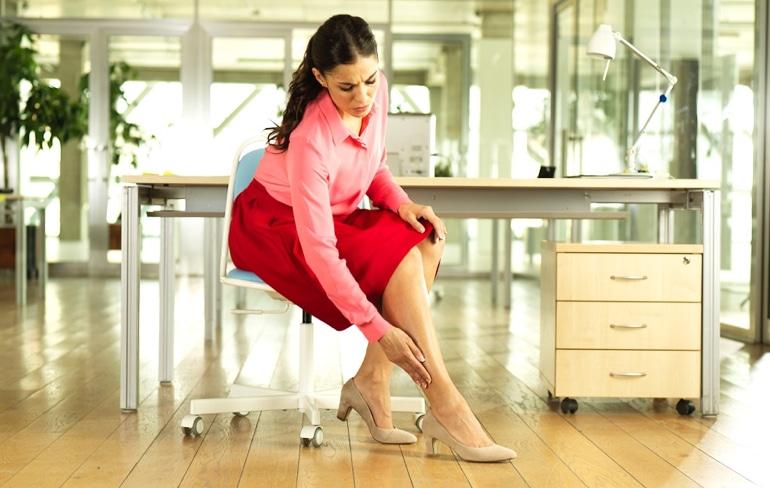 Moteris sėdi biure kėdėje ir glosto koją