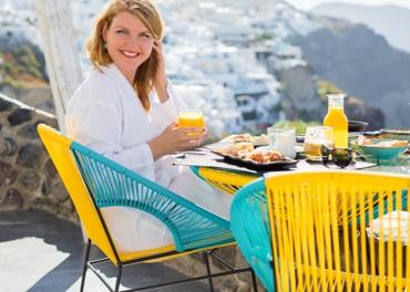Energinga besišypsanti moteris valgo sveikus pusryčius, kad užkirstų kelią venų nepakankamumui