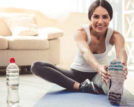 Moteris ant jogos kilimėlio atlieka venoms skirtus pratimus, apsaugančius nuo sunkumo jausmo kojose