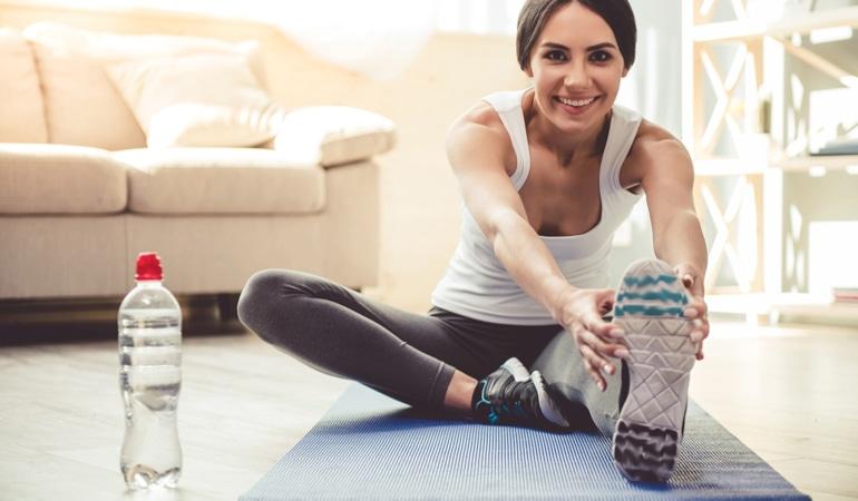 Moteris sėdėdama ant jogos kilimėlio lenkiasi pirmyn ir tempia abi kojas, siekdama apsisaugoti nuo venų nepakankamumo.